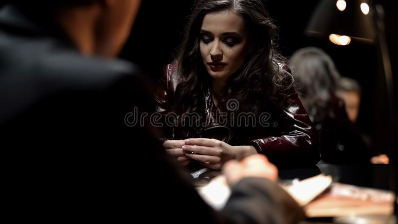 Female witness gives evidence in interrogation room, detective writing testimony. Stock photo royalty free stock photos