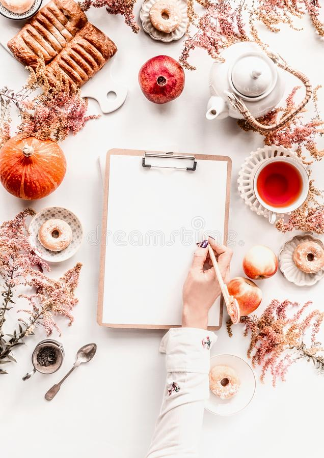 Free Female Woman Hand Writes On Blank White Piece Of Paper On Clipping Board  On Cozy Autumn Home Desk With Tea Setting, Cakes, Autumn Stock Images - 160350374
