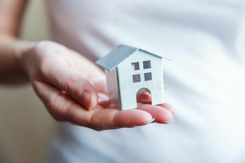 Female woman hands holding miniature white toy house. Female woman hands holding small miniature white toy house. Mortgage property insurance dream moving home royalty free stock photo
