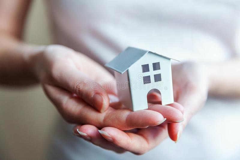 Female woman hands holding miniature white toy house. Female woman hands holding small miniature white toy house. Mortgage property insurance dream moving home stock photo