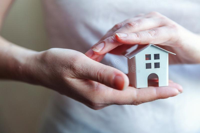 Female woman hands holding miniature white toy house. Female woman hands holding small miniature white toy house. Mortgage property insurance dream moving home royalty free stock photos