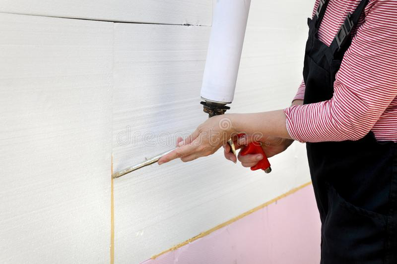 House renovation, polystyrene wall insulation. Female worker applying adhesive glue to styrofoam, polystyrene insulation of wall using applicator gun stock photos