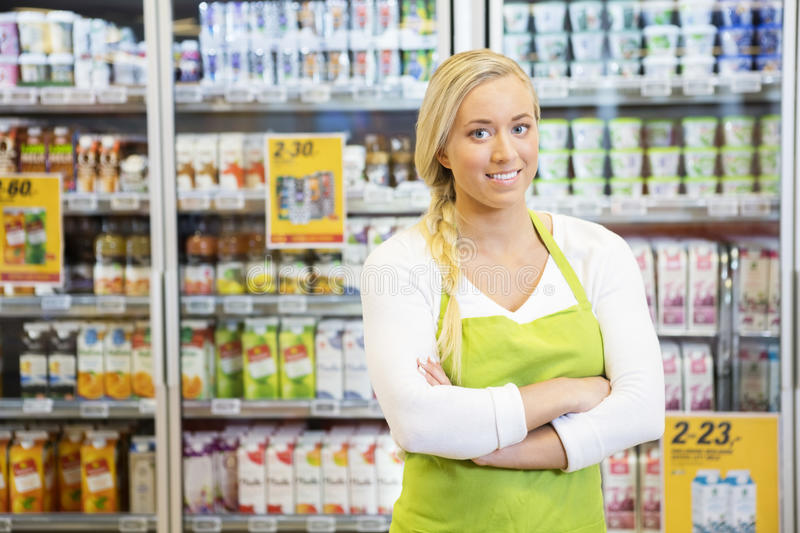 Female Worker With Arms Crossed In Grocery Store. Portrait of confident female worker with arms crossed smiling in grocery store royalty free stock image