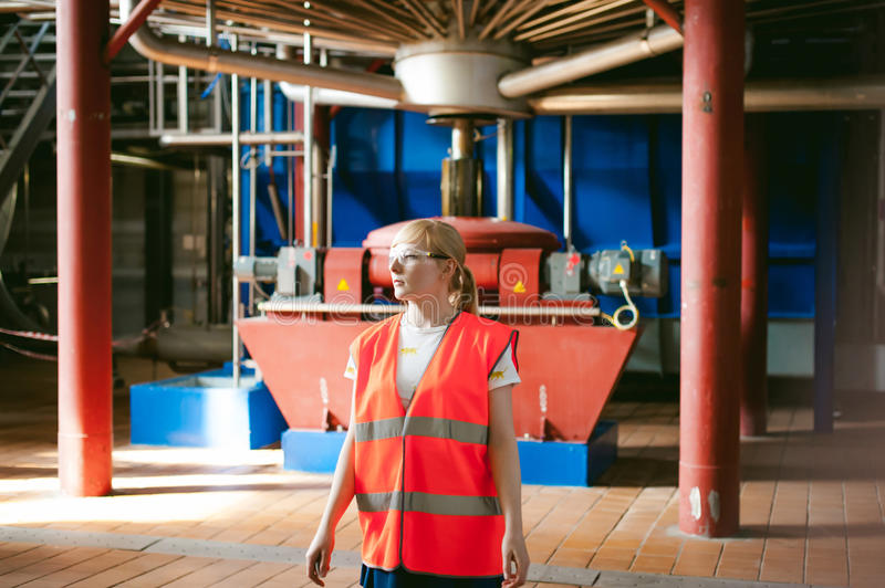 Female worker on beer factory. portrait woman in robe, standing on background line Food production, Inspection management control stock images
