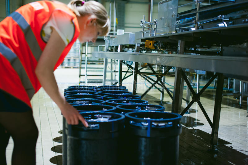Female worker on beer factory. portrait woman in robe, standing on background line Food production, Inspection management control stock photography