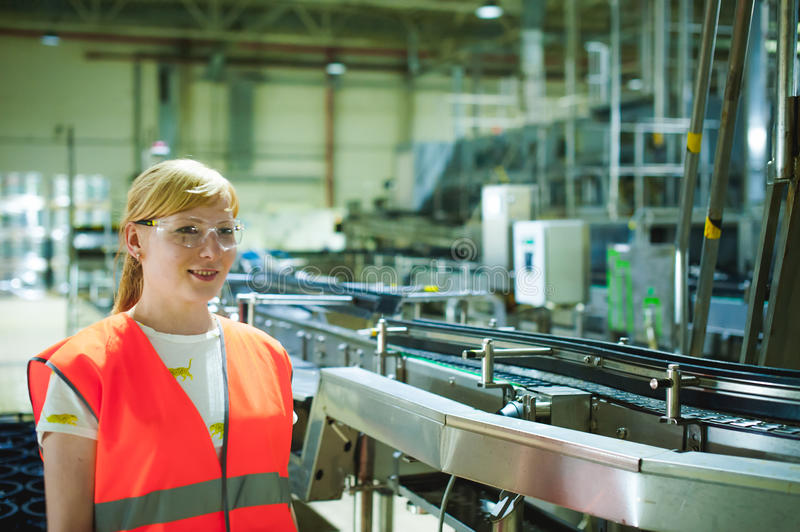 Female worker on beer factory. portrait woman in robe, standing on background line Food production, Inspection management control royalty free stock photography
