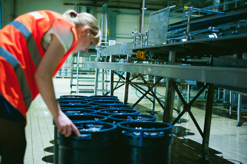 Female worker on beer factory. portrait woman in robe, standing on background line Food production, Inspection management control stock image