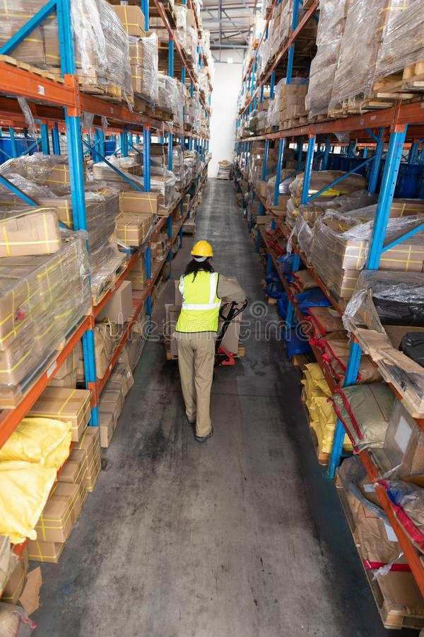 Female worker carrying cardboard boxes on pallet jack in warehouse. High angle view of female worker carrying cardboard boxes on pallet jack in warehouse. This royalty free stock images