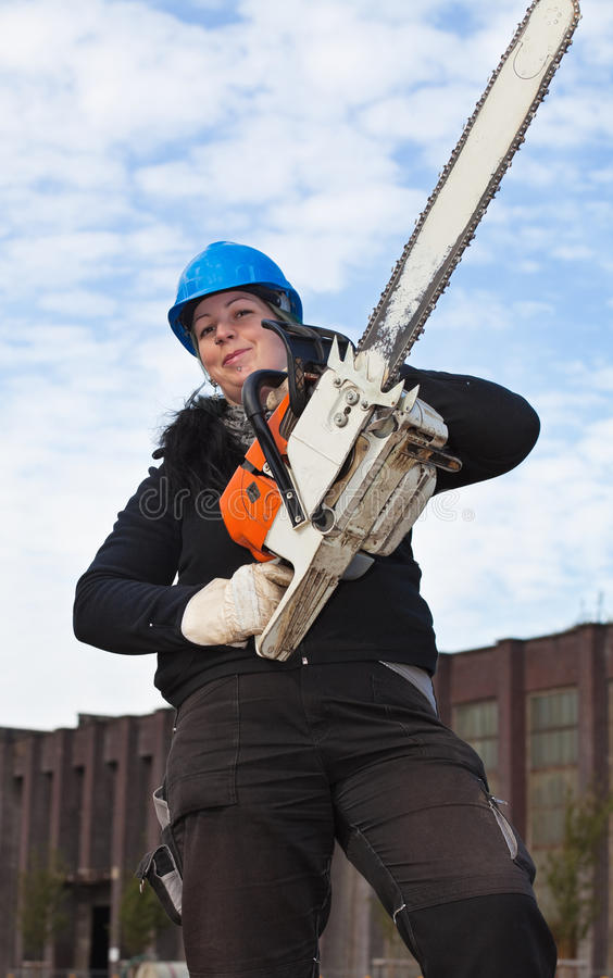 Female worker with chainsaw. Female worker in workwear and hardhat holds large chainsaw royalty free stock image