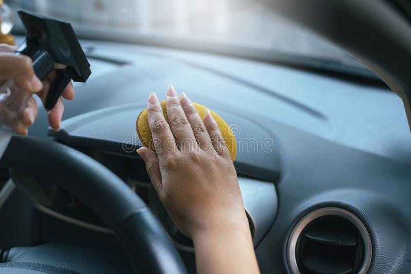 Female worker cleaning car inside dashboard,using waxy applying polish in car stock images