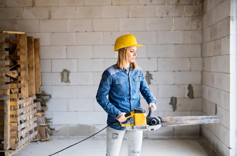 Young woman worker with saw on the construction site. stock image