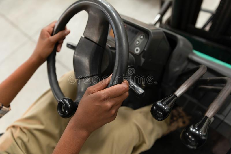 Female worker driving forklift in warehouse. Close-up of female worker driving forklift in warehouse. This is a freight transportation and distribution warehouse stock image