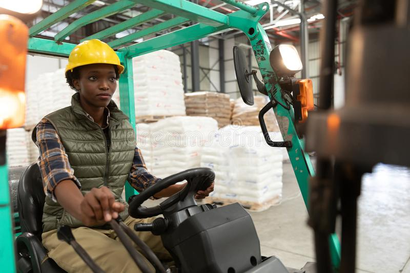Female worker driving forklift in warehouse. Front view of female worker driving forklift in warehouse. This is a freight transportation and distribution royalty free stock photo