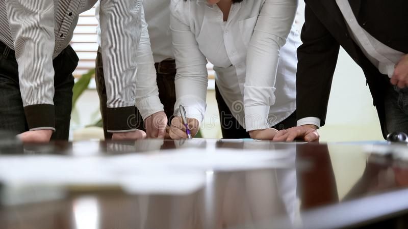Female worker explaining data in monthly report, teamwork at business meeting stock photo