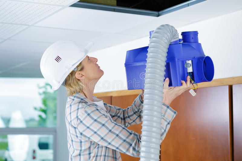 Female worker fitting ventilation system in buildings ceiling stock photo