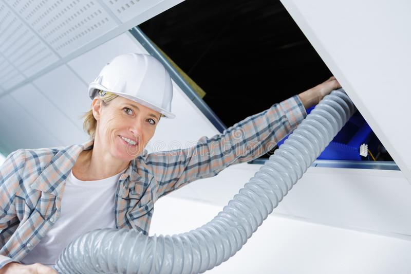 Female worker fitting ventilation system in buildings ceiling stock photography