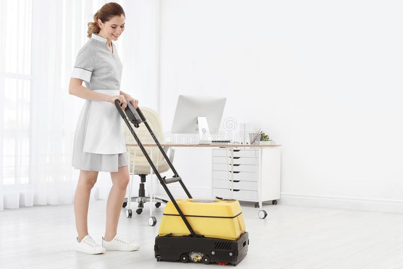 Female worker with floor cleaning machine, indoors. Female worker with floor cleaning machine indoors stock photos