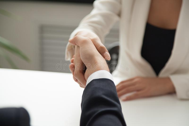 Female worker greeting business partner with handshake stock photography