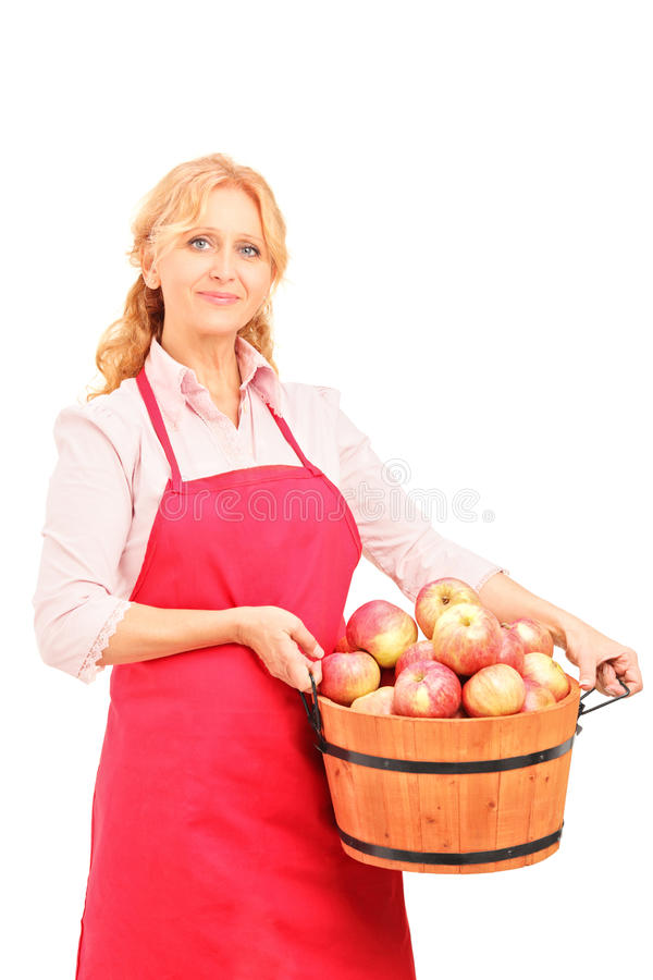 Download A Female Worker Holding A Basket Full Of Apples Stock Photo - Image: 27221062