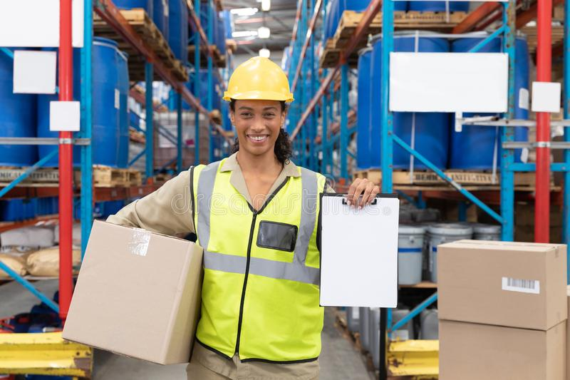 Female worker holding cardboard box and clipboard in warehouse. Happy female worker holding cardboard box and clipboard in warehouse. This is a freight stock photo