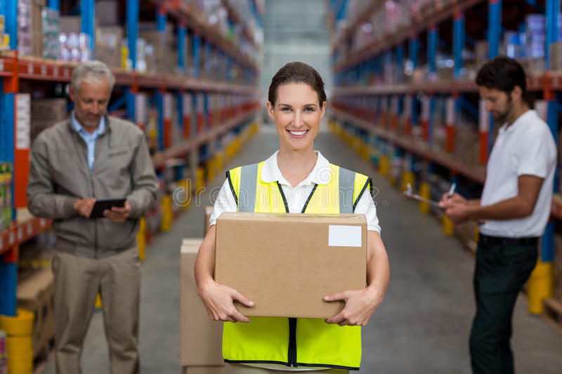 Female worker holding cardboxes while colleague working in background stock images