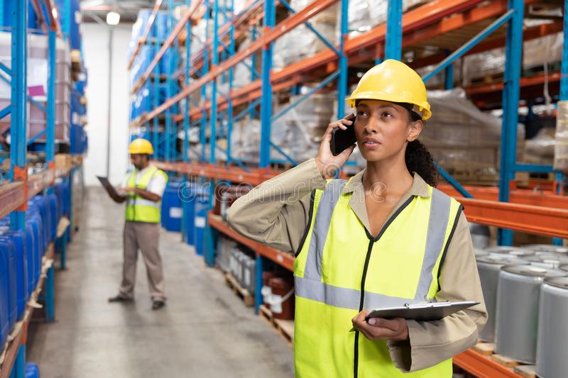 Female worker holding clipboard and talking on mobile phone in warehouse. Front view of female worker holding clipboard and talking on mobile phone in warehouse stock photo