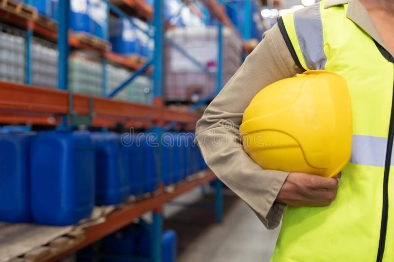 Female worker holding hard hat in warhouse. Mid section of female worker holding hard hat in warhouse. This is a freight transportation and distribution royalty free stock images