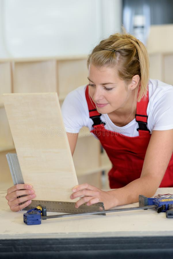 Female worker inspecting processed industrial board. Female worker inspecting a processed industrial board royalty free stock photo