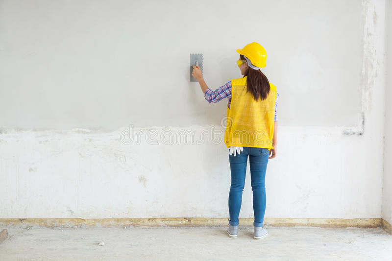 Female Worker, Labor Plastering White Concrete Wall at Home, House Construction Site royalty free stock photo