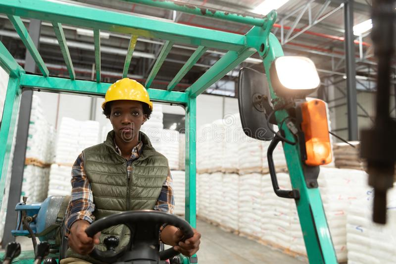 Female worker looking at camera while driving forklift in warehouse. Front view of female worker looking at camera while driving forklift in warehouse. This is a stock image