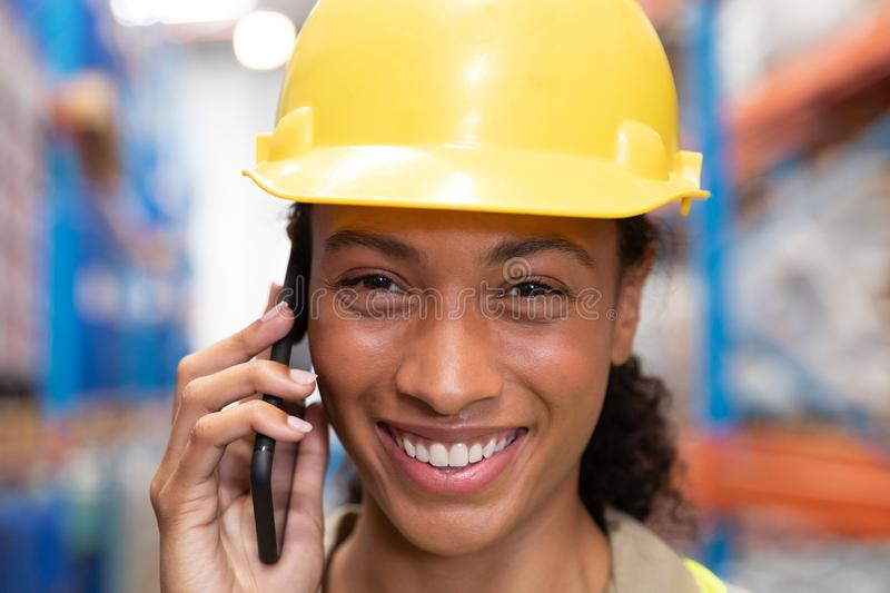 Female worker looking at camera while talking on mobile phone in warehouse. Close-up of female worker looking at camera while talking on mobile phone in stock photos