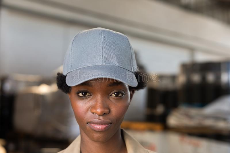 Female worker looking at camera in warehouse. Close-up of female worker looking at camera in warehouse. This is a freight transportation and distribution stock photography