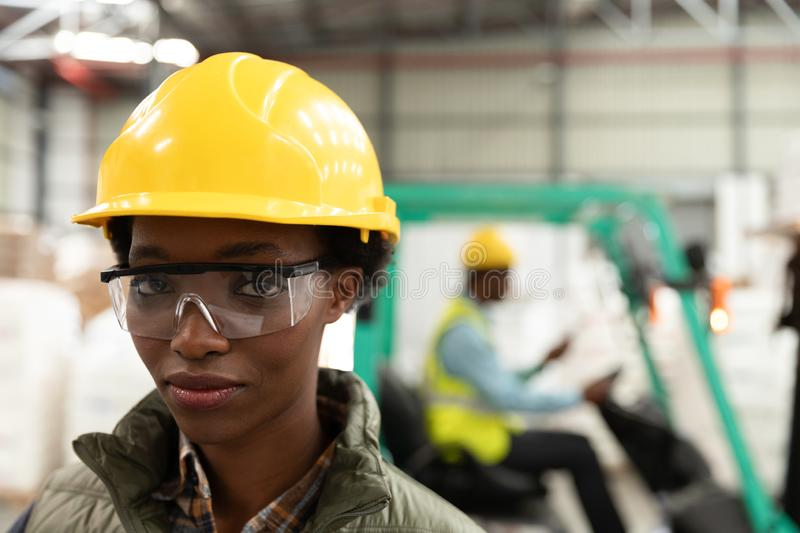 Female worker looking at camera in warehouse. Close-up of female worker looking at camera in warehouse. This is a freight transportation and distribution stock photo