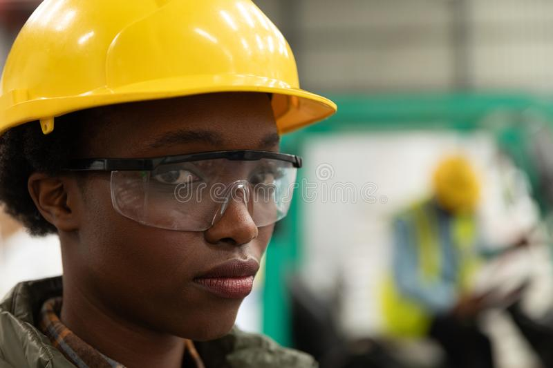 Female worker looking at camera in warehouse. Close-up of female worker looking at camera in warehouse. This is a freight transportation and distribution stock image