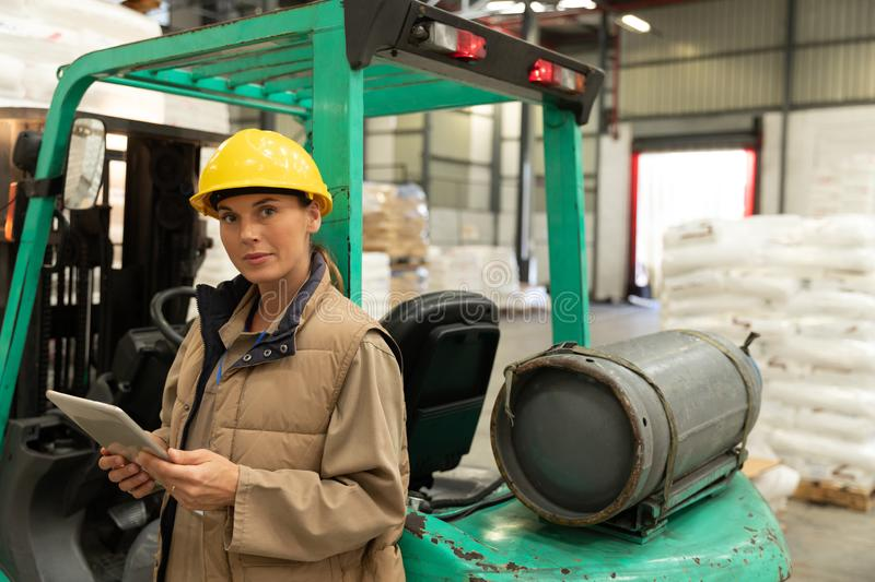 Female worker looking at camera while working on digital tablet in warehouse. Beautiful female worker looking at camera while working on digital tablet in stock image