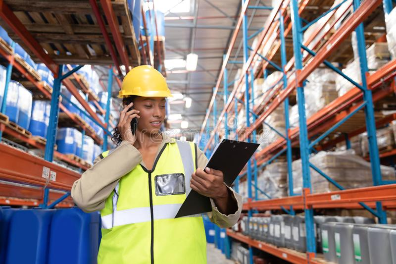 Female worker looking at clipboard while talking on mobile phone in warehouse. Front view of female worker looking at clipboard while talking on mobile phone in stock photos
