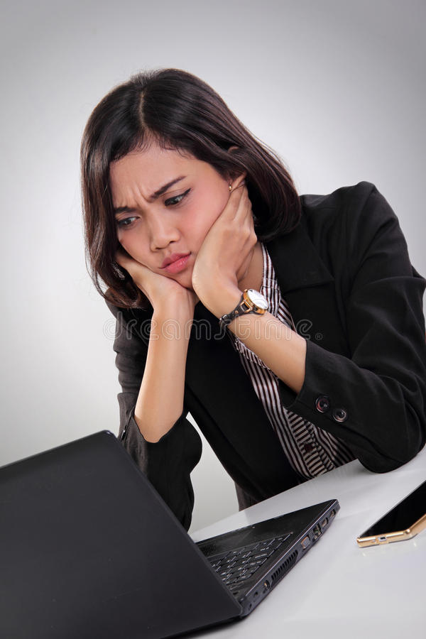Female worker looking at laptop in frustration. Portrait of an Asian female worker sitting in frustration while watching something at her laptop screen on the stock photography
