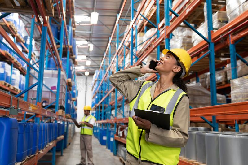 Female worker looking up while talking on mobile phone in warehouse. Front view of female worker looking up while talking on mobile phone in warehouse. This is a royalty free stock photography