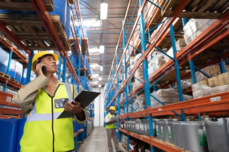 Female worker looking up while talking on mobile phone in warehouse. Front view of female worker looking up while talking on mobile phone in warehouse. This is a stock photos