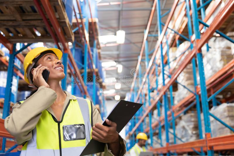 Female worker looking up while talking on mobile phone in warehouse. Front view of female worker looking up while talking on mobile phone in warehouse. This is a stock photo