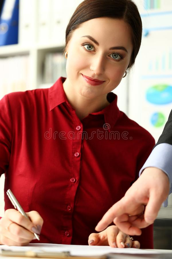 Female worker making notes in documents where male boss arm showing with finger royalty free stock photos