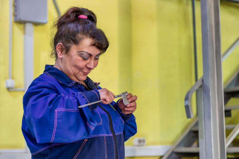 Female worker measures a part made on a waterjet machine. Stage control of finished products. Moscow, Russia - june 18, 2019: Female worker measures a part made royalty free stock image