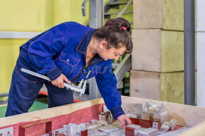 Female worker measures a part made on a waterjet machine. Stage control of finished products. Moscow, Russia - june 18, 2019: Female worker measures a part made royalty free stock images