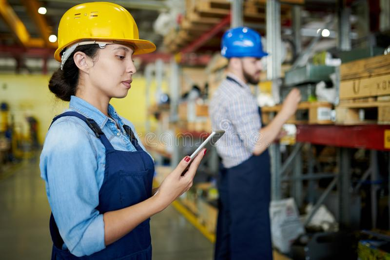 Female Worker Reviewing Stock. Side view portrait of female factory worker wearing hardhat using digital tablet in workshop with another worker in background royalty free stock photography