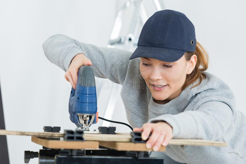 Female worker sawing wood stock photos