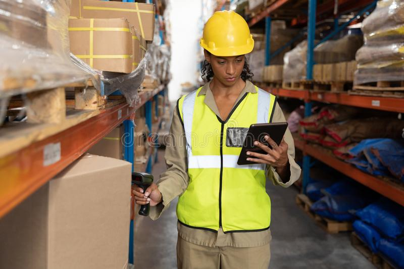 Female worker scanning package with barcode scanner while using digital tablet in warehouse. Front view of female worker scanning package with barcode scanner royalty free stock image