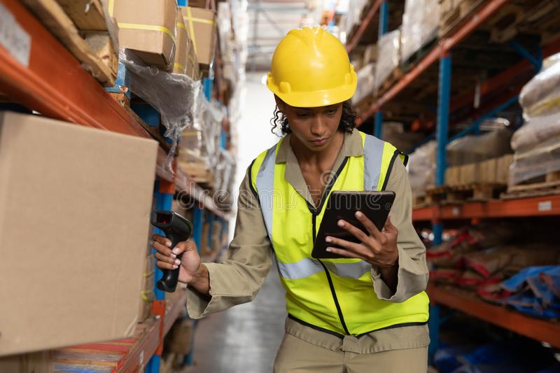 Female worker scanning package with barcode scanner while using digital tablet in warehouse. Front view of female worker scanning package with barcode scanner royalty free stock photos