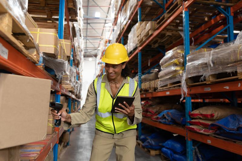 Female worker scanning package with barcode scanner while using digital tablet in warehouse. Front view of female worker scanning package with barcode scanner stock image