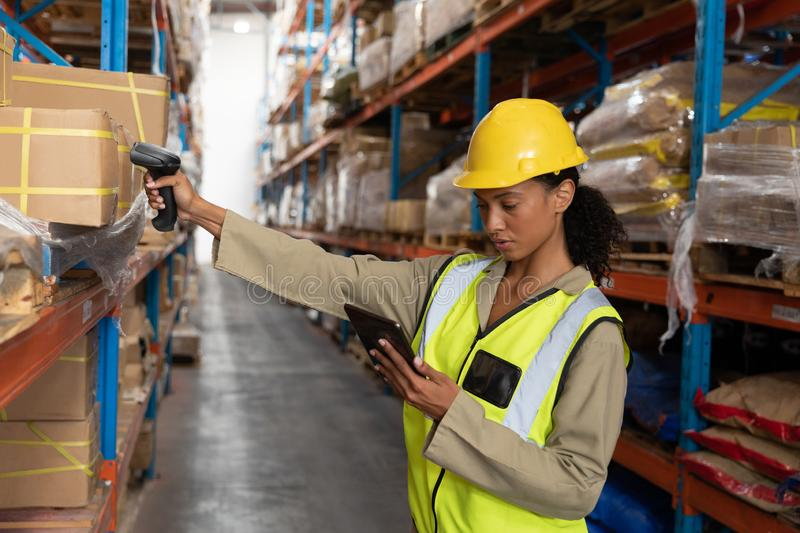 Female worker scanning package with barcode scanner while using digital tablet in warehouse. Side view of female worker scanning package with barcode scanner stock image