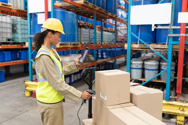 Female worker scanning package with barcode scanner while using digital tablet in warehouse. Side view of female worker scanning package with barcode scanner royalty free stock photo